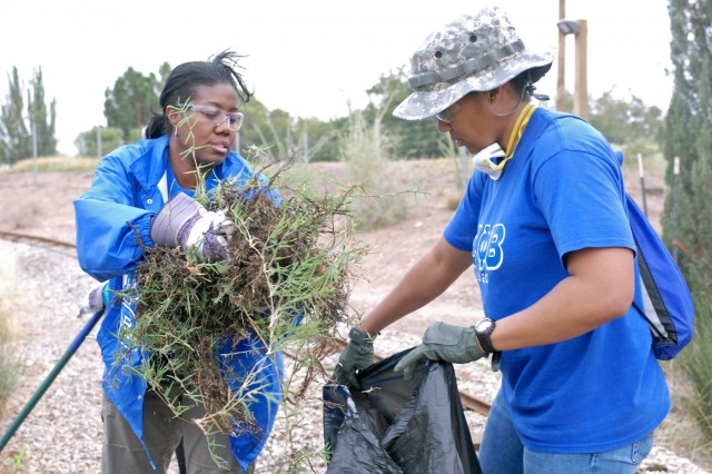 First Lt. Crystal Irving, the unit strength manager for 4th Brigade Combat Team, 1st Armored Division, holds up a garbage bag while Sgt. 1st Class Patricia Coleman, a senior enlisted advisor assigned to the 1st Brigade Combat Team, 1st Armored Division prepares to dispose of weeds and other debris during a Fort Bliss Army Volunteer Corps project at the El Paso Zoo, Sept. 8. In addition to volunteering as part of Team Bliss, Irving, a native of Columbus, Ga., and Coleman, a native of Tampa, Fla., were also representing the University of El Paso's Zeta Phi Beta Sorority. As part of the 9/11 National Day of Service and Remembrance, the UTEP Sorority was one of many different organizations that participated in 20 different projects that focused on giving back and bettering the El Paso, Texas community.U.S. Army photo by: Sgt. Terence Ewings, 24th Press Camp Headquarters.