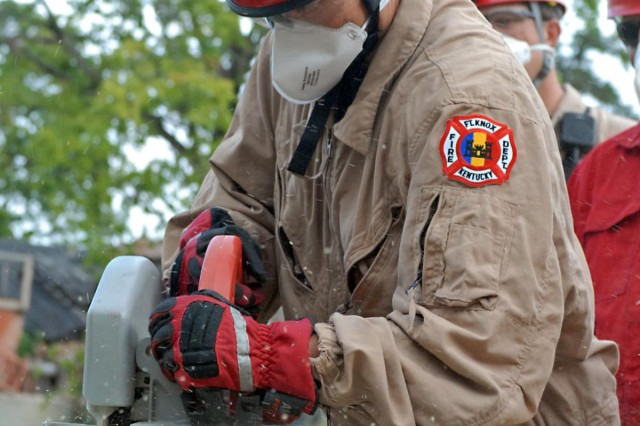 Betty Townsend, a firefighter with the Fort Knox Fire Protection Team, uses a circular saw to cut treated wood to use to brace and secure objects within a collapsed rubble pile during a Vibrant Response 13 search and rescue exercise at the Muscatatuck Urban Training Complex in Rineyville, Ky., Aug. 10, 2012. Townsend and other firefighters used different rescue tools to secure the surrounding area and extract mannequins, acting as civilians, from the area during the homeland disaster training venue. (U.S. Army photo by Sgt. Terence Ewings/Released)