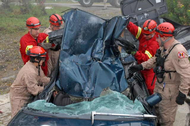 Firefighters assigned to the Fort Knox Fire Protection Team, lift the vehicle's roof off  and prepare to rescue a mannequin, posing as a trapped civilian inside the wreckage during a Vibrant Response 13 search and rescue exercise at the Muscatatuck Urban Training Complex, Rineyville, Ky., Aug. 10, 2012. The irefighters were responsible for evacuating injured civilians trapped underneath rubble and in vehicles during the homeland disaster training. (U.S. Army photo by Sgt. Terence Ewings/Released)