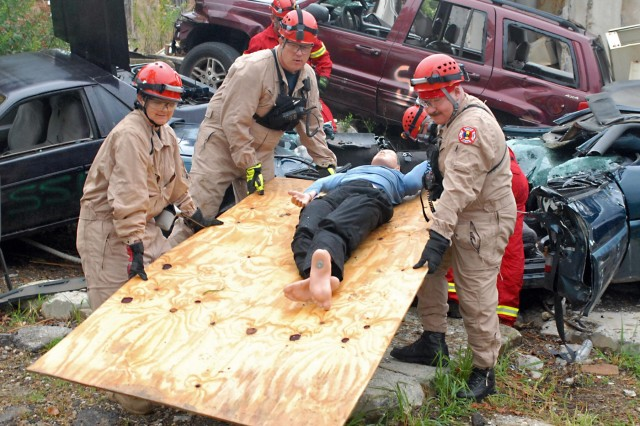 Fireman with the Fort Knox Fire Protection Team, use an improvised field litter to carry  a mannequin, posing as a civilian that was trapped inside a wrecked car, to safety during a Vibrant Response 13 search and rescue exercise at the Muscatatuck Urban Training Complex in Rineyville, Ky., Aug. 10, 2012. The firefighters used different rescue tools to secure the surrounding area and extract mannequins from the collapsed structure rubble pile training venue. (U.S. Army photo by Sgt. Terence Ewings/Released)