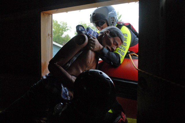 With the help of another rescue technician, Betty Townsend, a fireman assigned to the Fort Knox Fire Protection Team, attempts to move, and lift a mannequin, posing as a non-ambulatory injured civilian, through a small window opening of a house and into a water raft during a Vibrant Response 13 water rescue exercise at the Muscatatuck Urban Training Complex, Aug. 9. The Fort Knox Firemen from Rineyville, Ky., were responsible for evacuating injured civilians trapped in houses and vehicles within a flooded residential area.