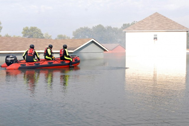 After performing area reconnaissance in a commercial water raft, firemen assigned to the Fort Knox Fire Protection Team prepare to enter a flooded residential area to evacuate injured civilians trapped in houses and vehicles during a Vibrant Response 13 water rescue exercise at the Muscatatuck Urban Training Complex, Aug. 9. Upon entering the smokey training venue, the Kentucky Firemen from Rineyville, Ky., utilized their technical rescue skills to complete the Vibrant Response homeland disaster training venue, conducted by U.S. Northern Command and led by U.S. Army North.