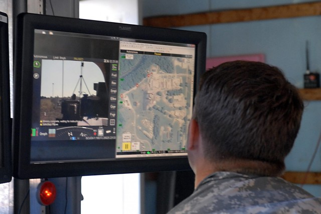 Spc. John Shilibear, a chemical specialist assigned to the 20th Support Command (chemical, biological, radiological, nuclear and high-yield explosives or CBRNE) monitors projected images cast from an advanced ground sample collection platform during a robotic test at the Muscatatuck Urban Training Center, Ind, Aug. 6. Shilibear, a native of Sumter, S.C., remotely controlled the robotic system during the test phase. The robotic system, developed by the Defense Threat Reduction Agency, is designed to allow operational forces to perform radiation reconnaissance and ground sampling missions after a nuclear detonation. The robotic system can be controlled manually or remotely. This reduces the need to send soldiers into a contaminated area.