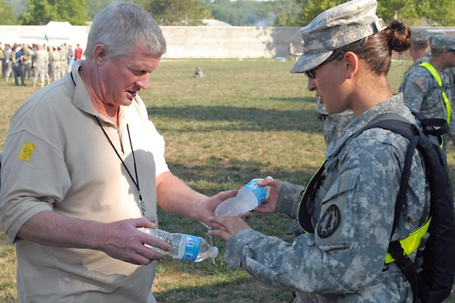 Spc. Stephanie Ciminelli, a military policeman assigned to the 401st Military Police Company, 720th Military Police Battalion, 89th Military Police Brigade out of Fort Hood, Texas, hands a bottle of water to an actor, portraying a displaced citizen, during a Vibrant Response 13 training exercise at a soccer stadium located on the Muscatatuck Urban Training Center, Ind., July 26. The Fort Hood troopers were responsible escorting civilians into the stadium and aiding the Federal Emergency Management Agency and Red Cross in handing-out food and water to the displaced civilians.