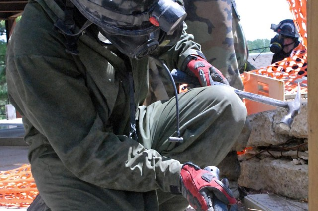 A Marine assigned to the Chemical, Biological Incident Response Force uses a hammers wooden bracing together to support a collapsing building during a Vibrant Response 13 field training exercise at the Muscatatuck Urban Training Center, Ind., July 29. The CBIRF unit was responsible for decontaminating, treating and evacuating displaced civilians in the collapsed building. During the simulated training exercise, the rescue technicians used high-powered tools and equipment to maneuver through the four levels of the infrastructure so they could safely evacuate civilians during the training venue.