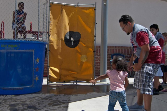 Children from the Fort Bliss community line up and throw rubber balls at the dunk tank release lever in an attempt to unseat Michael J. Dunn Jr., the 'for age' president at the Milam Youth Activity Center, from his position atop the device during the Fort Bliss MYAC's 2nd Annual Block Party, April 21. The festive event, which was coordinated by the staff and Fort Bliss teens at the MYAC, was conducted to recognize the contributions and sacrifices made by the installation's military youth.