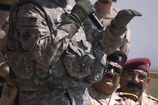 Maj. Gen. David G. Perkins, U.S. Division-North and 4th Infantry Division commanding general, congratulates Iraqi soldiers assigned to 3rd Battalion, 11th Brigade, 3rd Iraqi Army Division, after the completion of their month-long training rotation at Ghuzlani Warrior Training Center, March 31. Prior to shaking hands with the Task Force Ironhorse commander, the Iraqi soldiers showcased their enhanced fire and maneuver combat skills during a culminating battalion level live fire exercise during Tadreeb al Shamil. Tadreeb al Shamil, Arabic for All Inclusive Training, is an Iraqi Ground Forces Command training initiative to develop and strengthen IA units' capabilities to secure and defend the people of Iraq from external threats to Iraq's sovereignty.