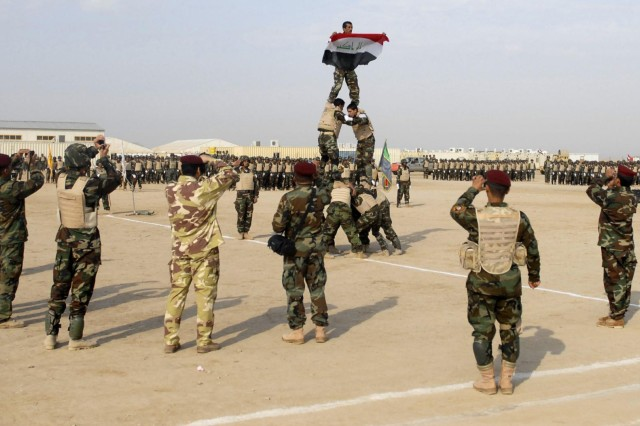 Graduating troops from the 41st Brigade, 10th Division Iraqi army assemble a pyramid with the Iraqi on the highest level displaying an Iraqi flag at the IA graduation at the Besmaya Range Complex, Dec. 31, 2008.