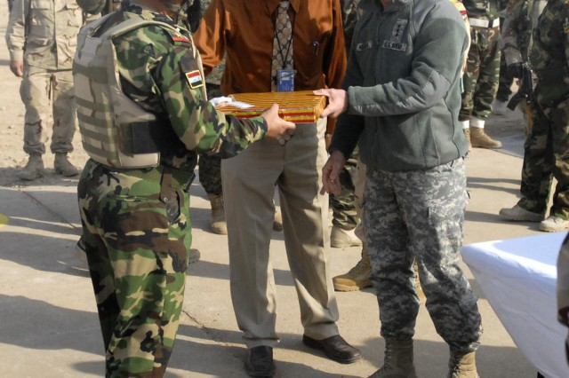 Lt. Gen. Frank Helmick, commander of Multi-National Security Transition Command Iraq, presents one of the Iraqi Army graduates in the 41st Brigade, 10th Division Iraqi Army with a gift at the Iraqi army graduation at the Besmaya Range Complex, Dec. 31, 2008.