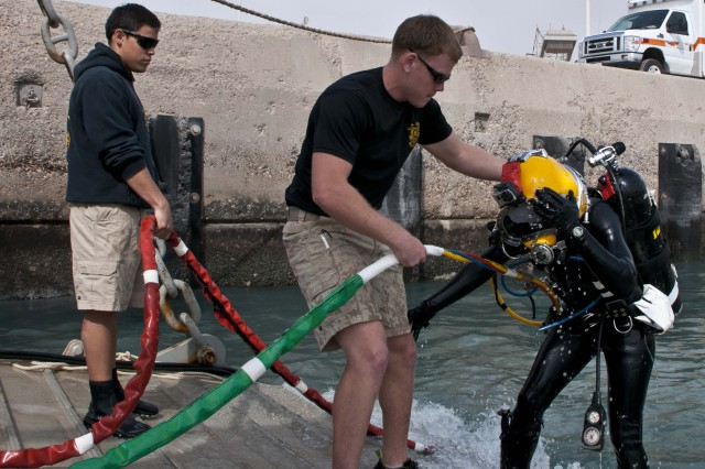 Pfc. Brendan Milham, a diver with the 74th Engineer Dive Detachment, who is deployed from Joint Base Langley-Eustis, Va., tends to 1st. Lt. Christie Plackis, the fourth female diver in the history of the Army, who serves as the executive officer for the 74th EDD, after she completed underwater chainsaw training, March 6, 2013, at the Sea Point of Debarkation/Embarkation, Shuaiba Port, Kuwait. Every diver uses a fellow diver, tender, to exit the water safely while wearing gear in excess of 100 lbs.