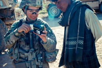 Staff Sgt. Claudia Caberoherbas, Female Engagement Team, Combined Task Force (CTF) 4-2, prints out a photo to give to the children during Operation Southern Fist III, March 4, in Kandahar province, Afghanistan. (U.S. Army photo by 2nd Lt. Jennifer Fr...
