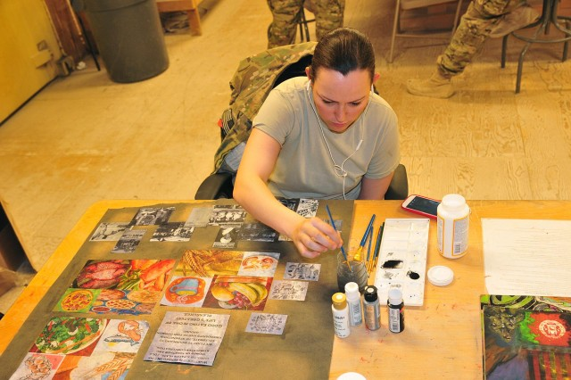 """Spc. Sarah Stimpson, an information technology specialist with Combined Task 4-2 (4th Stryker Brigade Combat Team, 2nd Infantry Division), works on a """"thank you"""" collage for the workers of the dining facility March 19 on Forward Operating Base Masum Ghar in the Panjwa'i district of Afghanistan. Stimpson, a Strafford, N.H., native, creates artwork for fellow soldiers during her personal time while deployed to Afghanistan in support of Operation Enduring Freedom. (U.S. Army photo by Sgt. Kimberly Hackbarth, 4th SBCT, 2nd Infantry Division Public Affairs Office)"""