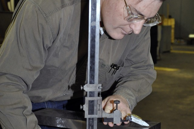 First year apprentice Brian Martino measures the tolerances on a breech block for a 105mm howitzer.