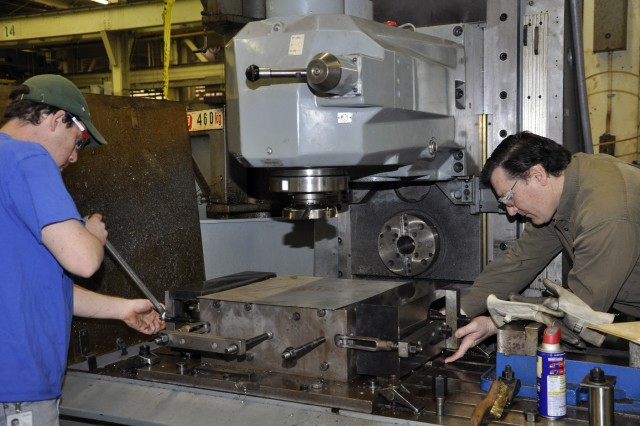 Apprentice Brian Martino, right, with mentor and machinist Benjamin Noxon working on two M20 breech blocks for a 105mm howitzer system.