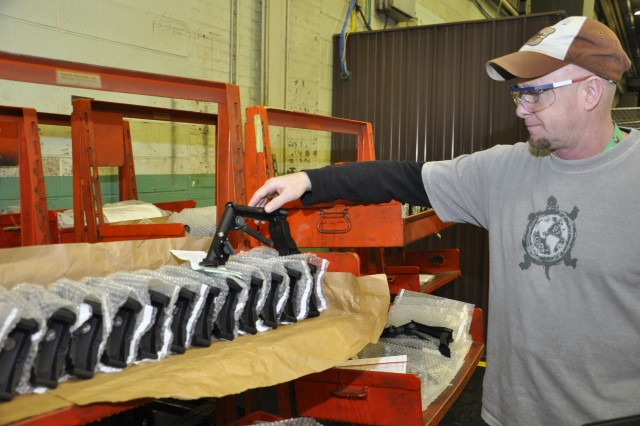 Arsenal expediter Mike Smith is checking the finished handles for 60mm mortar systems.  Smith began working at the Arsenal about five months ago.