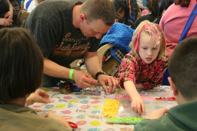 FORT CARSON, Colo. -- Staff Sgt. Kenneth Coffee, 1st Battalion, 68th Armor Regiment, 3rd Brigade Combat Team, 4th Infantry Division, assists his daughter, Ryleigh, with a bead craft at the Child, Youth and School Services table, Saturday during Eggsperience.