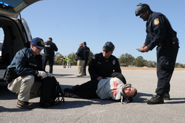 Spc. Jason Clare, 164th TAOG, plays as an injured bystander, and is searched for wounds and weapons during the Fort Rucker All Hazards Exercise March 13.