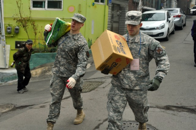 """Pfc. Tyler. D. Russell, human resource specialist at the USAG-Y Headquarters and Headquarters Company orderly room, and Capt. Vladislav Silayev, the company commander for HHC of USAG Yongsan deliver rice and instant noodles to elderly citizens and low income families, here, Mar. 19. """" - U.S. Army photo by Pfc. Jung-Ji-hoon"""