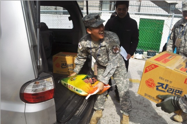 Cpl. Jaekyung Lee, administration specialist at the USAG-Y ROKA Support Office,  delivers rice and instant noodles to elderly citizens and low income families, here, Mar. 19. - U.S. Army photo by Pfc. Jung-Ji-hoon