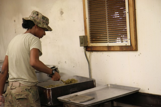"""PAKTIKA PROVINCE, Afghanistan """" U.S. Army Pfc. Shaneika L. Jackson, a cook  assigned to Company E, 210 Brigade Support Battalion, Task Force """"Golden Dragons,"""" 2/10 Security Forces Assistance Brigade, Forward Operating Base Boris, stirs green beans for the dinner meal March 12, 2013. (Photo by U.S. Army Sgt. Mark A. Moore II, 2/10 Security Forces Assistance Brigade Public Affairs)"""