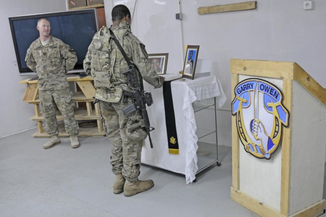 U.S. Army chaplain Capt. Matthew Burden, (left) a native of Little Rock, Ark., assigned to 2nd Battalion, 7th Cavalry Regiment, 4th Brigade Combat Team, 1st Cavalry Division, based out of Fort Hood, Texas., watches as a soldier pays his final respect during a ceremony to honor Inez Renee Baker, a civilian contractor who was killed during an insider attack on Forward Operating Base Tagab, in the eastern part of Kapisa province, March 18, 2013. Baker served in the U.S. Army for 26 years before moving to the private sector and work in Afghanistan as an adviser last year. The memorial ceremony brought coalition forces and civilian contractors together to honor Baker's contribution to the fight. (U.S. Army photo by Staff Sgt. Richard Andrade, 4th BCT, 1st Cavalry Division Public Affairs)