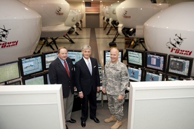 In the Warrior Hall Flight Simulation Training Facility at Fort Rucker, Ala., Secretary of the Army John McHugh (center), Civilian Aide to the Secretary of the Army, Mr. G. Mack Dove and  Maj. Gen. Kevin W. Mangum, Commanding General of the Aviation Center of Excellence and Fort Rucker  take time for a photo oportunity at the flight simulator control cernter, March 19, 2013. (U.S. Army photo by Spc. John G. Martinez)