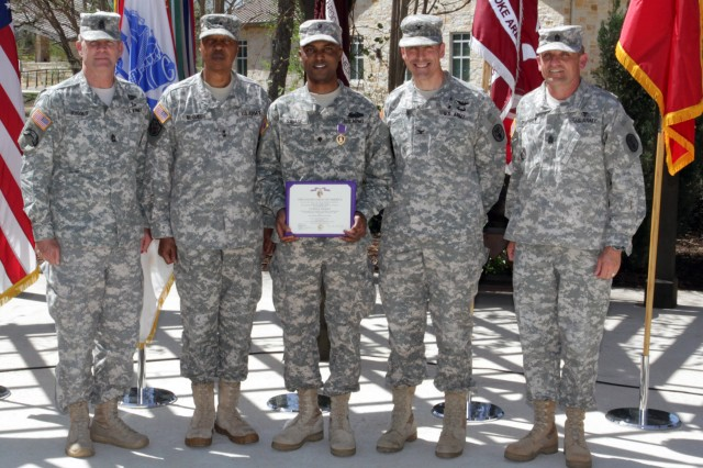 "FORT SAM HOUSTON, Texas "" Spc. Abdullah Savage (center), Company B, Warrior Transition Battalion, poses with (from left to right) Maj. Gen. Adolph McQueen Jr., Command Sgt. Maj. Hu Rhodes, Col. Kyle Campbell and Command Sgt. Maj. Mark Pumphrey March 18 following the presentation of the Purple Heart Medal at a ceremony in the Purple Heart Courtyard of the Warrior and Family Support Center. Savage was assigned to Company C, 2nd Battalion, 4th Infantry Regiment, 10th Mountain Division, when he was wounded in a vehicle-borne improvised explosive device attack on his combat outpost in Afghanistan. McQueen is the deputy commanding general for support, U.S. Army North (Fifth Army); Rhodes is the command sergeant major for Army North; Campbell is the commander for Brook Army Medical Center, and Pumphrey is his command sergeant major."