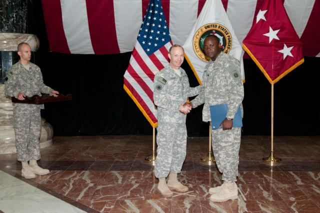 Spc. Ojumiri Mammah, a food service specialist with 307th Brigade Support Battalion, 1st Brigade, 82nd Airborne Division (Advise and Assist Brigade), is sworn in as a United States citizen by Lt. Gen. Charles Jacoby, at a ceremony Feb. 15, 2010, on Camp Victory, Iraq. Mammah is originally from Sierra Leone. (U.S. Army photo by Sgt. Michael J. MacLeod)