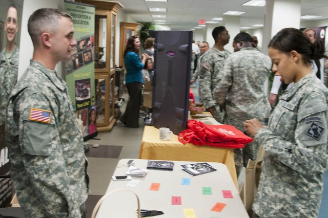 Spc. Patricia Huckoby, right, of the Warrior Transition Battalion, Co. C, speaks with Sgt. Neal Wiser, XVIII Airborne Corps, during the Community Resilience Fair, March 12, held in the Soldier Support Center. The fair provided resilience resources for servicemembers, Families and civilians.