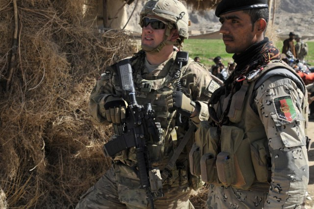"""U.S. Army Capt. Derek C. Knapp, from Austin, Texas, with Security Force Assistance Team 10, Texas Army National Guard, and his Afghan Border Police counterpart discuss security during a shura near the area known as the """"Jungle"""" during Operation Southern Fist III March 5, 2013, in the district of Spin Boldak, Kandahar province, Afghanistan. Insurgents use the Jungle during the summer fighting season as an infiltration route and cache site. (Army National Guard photo by Staff Sgt. Shane Hamann)"""