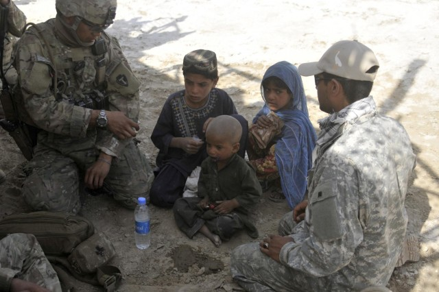 """Staff Sgt. Mangnan Tan, a medic from Lubbock, Texas, with Security Force Assistance Team 10, Texas Army National Guard, treats a child who approached his unit near an area known as the """"Jungle"""" during Operation Southern Fist III, March 6, 2013, in the district of Spin Boldak, Kandahar province, Afghanistan. Insurgents use the jungle during the summer fighting season as an infiltration route and cache site. The operation eliminated areas that could be used as concealment."""