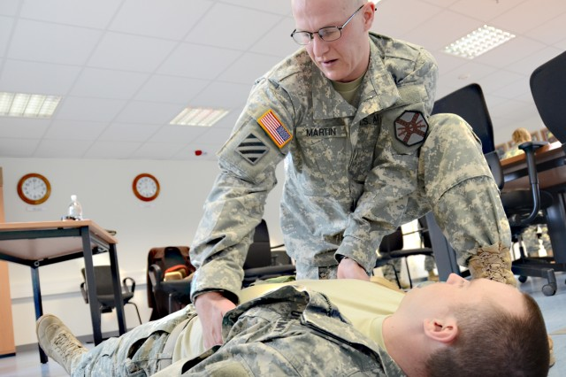 Sgt. David Martin, a chaplain's assistant for USAG Grafenwoehr's Headquarters and Headquarters Company, administers aid to a wounded Soldier, played by Sgt. Everett Ryder, Grafenwoehr's HHC, during the Warrior Task Battle Drill section of the SOY/NOY competition, March 19.