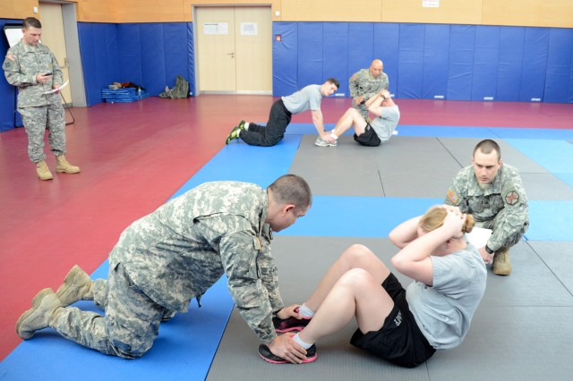 Participants of the 2013 Bavaria Military Community Best Warrior Competition push their limits while doing sit-ups during an Army Physical Fitness Test, March 19.