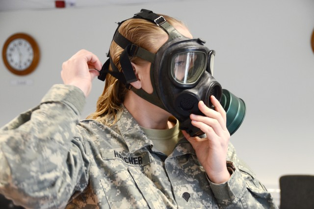 Spc. Shannon Hatcher, a military police officer stationed in Garmisch, dons a protective mask during the Warrior Task Battle Drill section of the SOY/NOY competition, March 19.