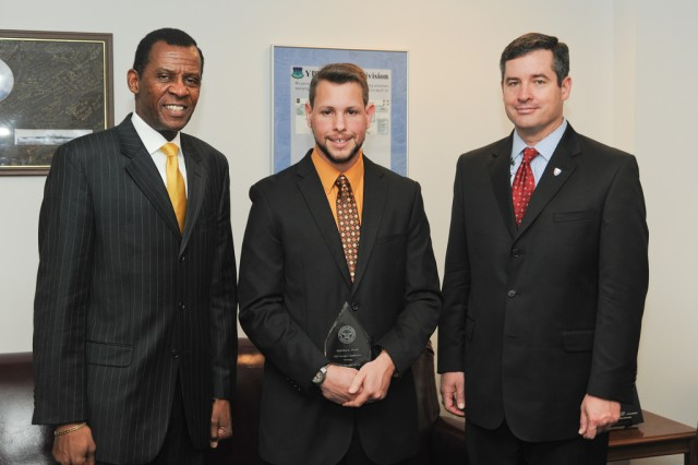Earl Wyatt (left), deputy assistant secretary of defense for rapid fielding, and Dale Ormond (right), director of the U.S. Army Research, Development and Engineering Command, recognize Matthew West, a junior hydra project engineer at RDECOM's Armament Research, Development and Engineering Center, with the Foreign Comparative Testing Program Manager of the Year for 2012, at the Pentagon, March 20, 2013.