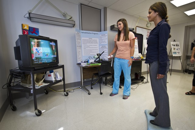 Shinnelle Moruf, an audiology graduate student from Colorado University, Boulder, Colo. and Certified Occupational Therapy Assistant Tania DeGuisti, demonstrate how technology like the video gaming systems Nintendo Wii helps improve balance, coordination, and cognition in patients suffering from Traumatic Brain Injury durng a Brain Injury Awareness Open House, March 21, 2013, at Tripler Army Medical Center in Honolulu. The Pacific Regional Medical Command's Traumatic Brain Injury Program, a comprehensive program which provides a continuum of integrated care and services for active duty service members and other beneficiaries with TBI.