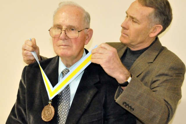 Henry J. Slavico (left) receives the Order of Saint Maurice from Col. (Ret.) John Mitchell, former Fort. Benning garrison commander.