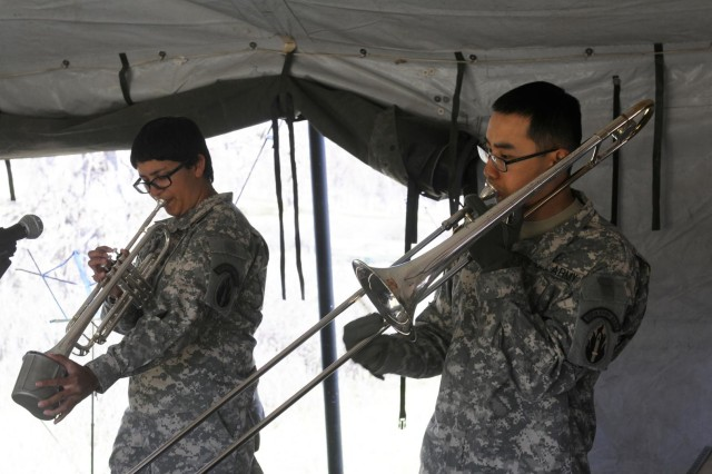 Army Spc. Natalie M. Salvatierra, left, of Temecula, Calif., uses a canteen cover as a mute on her trumpet while accompanying Staff Sgt. Kirk K. Wang of San Diego. Soldiers with the 300th Army Band, an Army Reserve unit based in Bell, Calif., performed concerts for the troops and practiced their combat skills during Warrior Exercise 91 13-01 at Fort Hunter Liggett, Calif. The joint exercise drew more than 3,500 soldiers, airmen and sailors from across the United States.