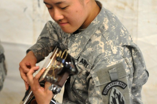 U.S. Army Staff Sgt. Grace J. Chin of Torrance, Calif., a percussionist with the 300th Army band, plays guitar during a dining facility concert.  Soldiers with the 300th Army Band, an Army Reserve unit based in Bell, Calif., performed concerts for the troops and practiced their combat skills during Warrior Exercise 91 13-01 at Fort Hunter Liggett, Calif. The joint exercise drew more than 3,500 soldiers, airmen and sailors from across the United States.