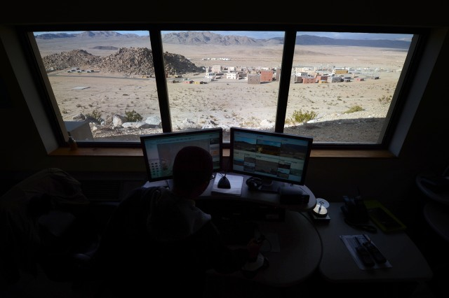 A computer operator watches screens displaying live interior and exterior images of the training town before him at the National Training Center, Fort Irwin, Calif., Feb. 20, 2013. The  2nd Brigade Combat Team, 1st Infantry Division from Fort Riley, Kan., is training at NTC as the first brigade to be aligned with AFRICOM.