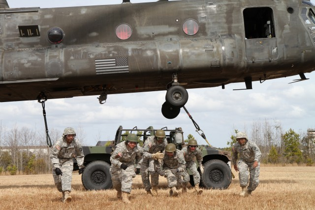 Instructors and students execute the correct way to exit from the High Mobility Multipurpose Wheeled Vehicle after sling loading it to a Chinook during a training exercise held at Fort Eustis, Va., March 11, 2013.