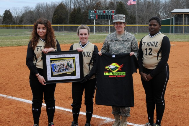 Brig. Gen. Kristin K. French, commanding general of the 3d ESC, receives a t-shirt and a signed plaque from the Fort Knox High School softball team before a game March 23 at Fort Knox High School. French was invited to the event to speak to the softball team and to throw the first pitch of the game. (U.S. Army photo by Sgt. Justin A. Silvers)