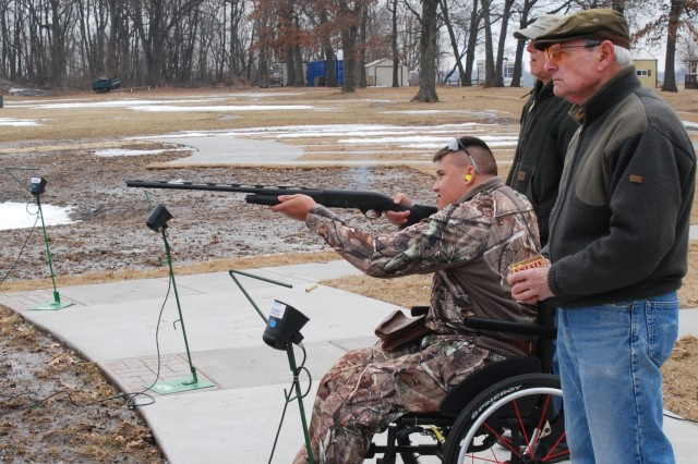 Before the hunt: Cpl. Quinton Picone practice shooting at a shooting range outside DeWitt, Iowa. Looking on are, L-R, Stan Currey and Stewart LeBlanc.