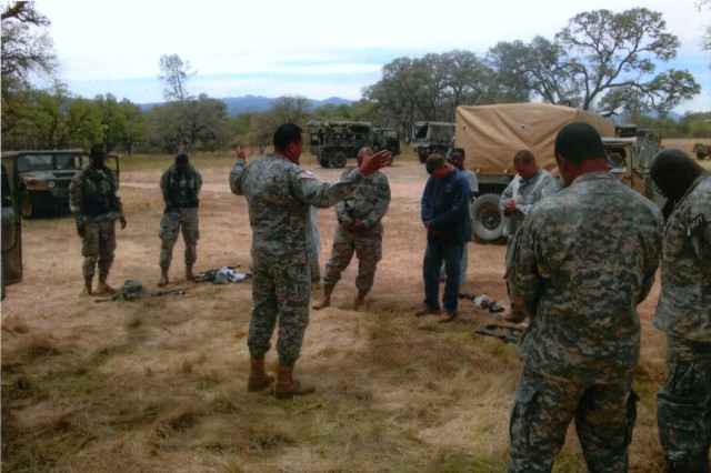 Capt. (CH) Evelio Rodriguez, prays with a group of soldiers during a field exercise.