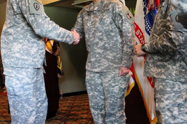 From left to right, U.S. Army Lt. Gen. Robert Brown, I Corps commanding general, presents Staff Sgt. Catherine Long with his coin as Command Sgt. Maj. John Troxell, I Corps senior enlisted adviser, looks on, March 22, 2013, during the team courage recognition awards Ccremony held at Joint Base Lewis-McChord, Wash. Long, a geospatial intelligence analyst with Headquarters Support Company, 7th Infantry Division, was nominated by her command because of her accomplishments as the only geospatial intelligence analyst in Headquarters Support Company, 7th Infantry Division.  (U.S. Army photo by Staff Sgt. Lindsey Kibler/Released)