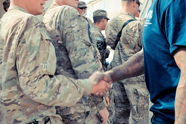 Soldiers with the 38th Engineer Company, 4th Brigade Combat Team, 2nd Infantry Division, greet Cleveland Browns linebacker D'Qwell Jackson (right), during his visit to Kandahar province, Afghanistan, March 18, 2013. The visit was part of a week-long NFL-USO morale-building tour.