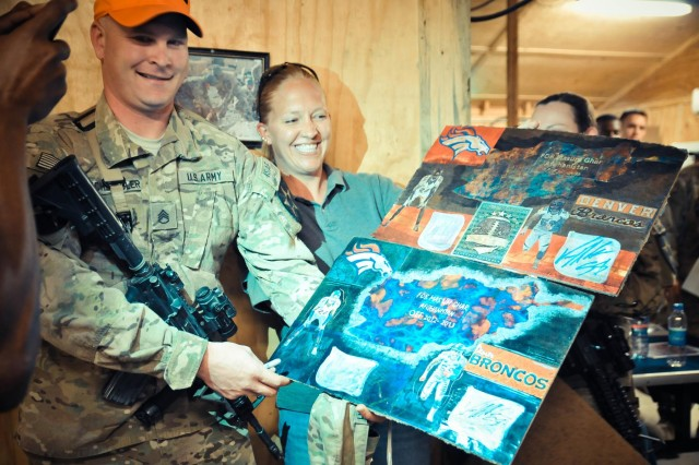 Staff Sgt. Jeremiah Hochstedler (left), with Headquarters and Headquarters Company, 4th Brigade Combat Team, 2nd Infantry Division, poses with posters featuring the Denver Broncos football team in Kandahar province, Afghanistan, March 18, 2013. The posters, created by a Soldier serving in Hochstedler's unit, were autographed by cornerback Champ Bailey and linebacker Vonn Miller during their visit to Afghanistan as part of an NFL-USO morale-building tour.