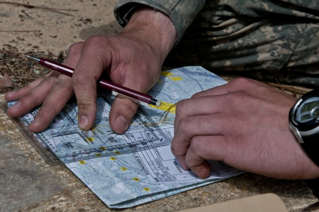 A candidate in the 82nd Airborne Division's Noncommissioned Officer and Trooper of the year competition reviews his map and points before setting off into the dense woods surrounding the division's Pre-Ranger Course, as part of the competition's land navigation event.