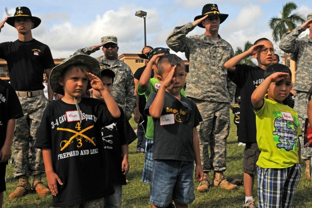 Soldiers of 3rd Squadron, 4th Cavalry Regiment, 3rd Brigade Combat Team, 25th Infantry Division, and junior Raiders, salute during the playing of the National Anthem to begin the Junior Spur Ride, March 21, 2013 on Schofield Barracks, Hawaii.