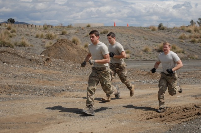 """KHOWST PROVINCE, Afghanistan  """" A three-man team run during the first leg of the obstacle course during the Forward Operating Base Salerno, Afghanistan, Mud Run, March 24, 2013.  More than 50 Soldiers from various units from the FOB participated in the course. The two-mile course featured 15 different obstacles that challenged the Soldiers physically and mentally, while adding the elements of water and mud to help make the course even more difficult. (U.S. Army photo by Sgt. 1st Class Abram Pinnington, TF 3/101 Public Affairs)"""
